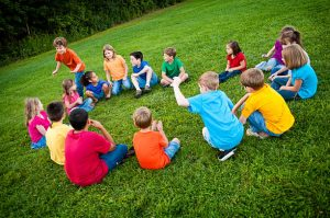 """Color photo of a group of boys and girls sitting in a circle and playing """"Duck, Duck, Goose!"""" in the grass."""